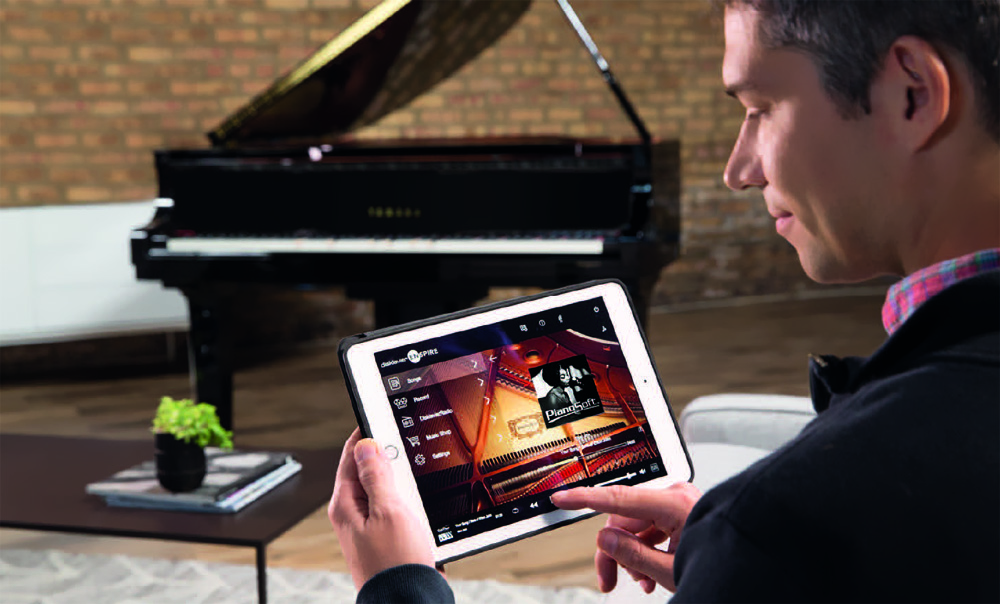 Man using an iPad to remotely control the Disklavier Enspire