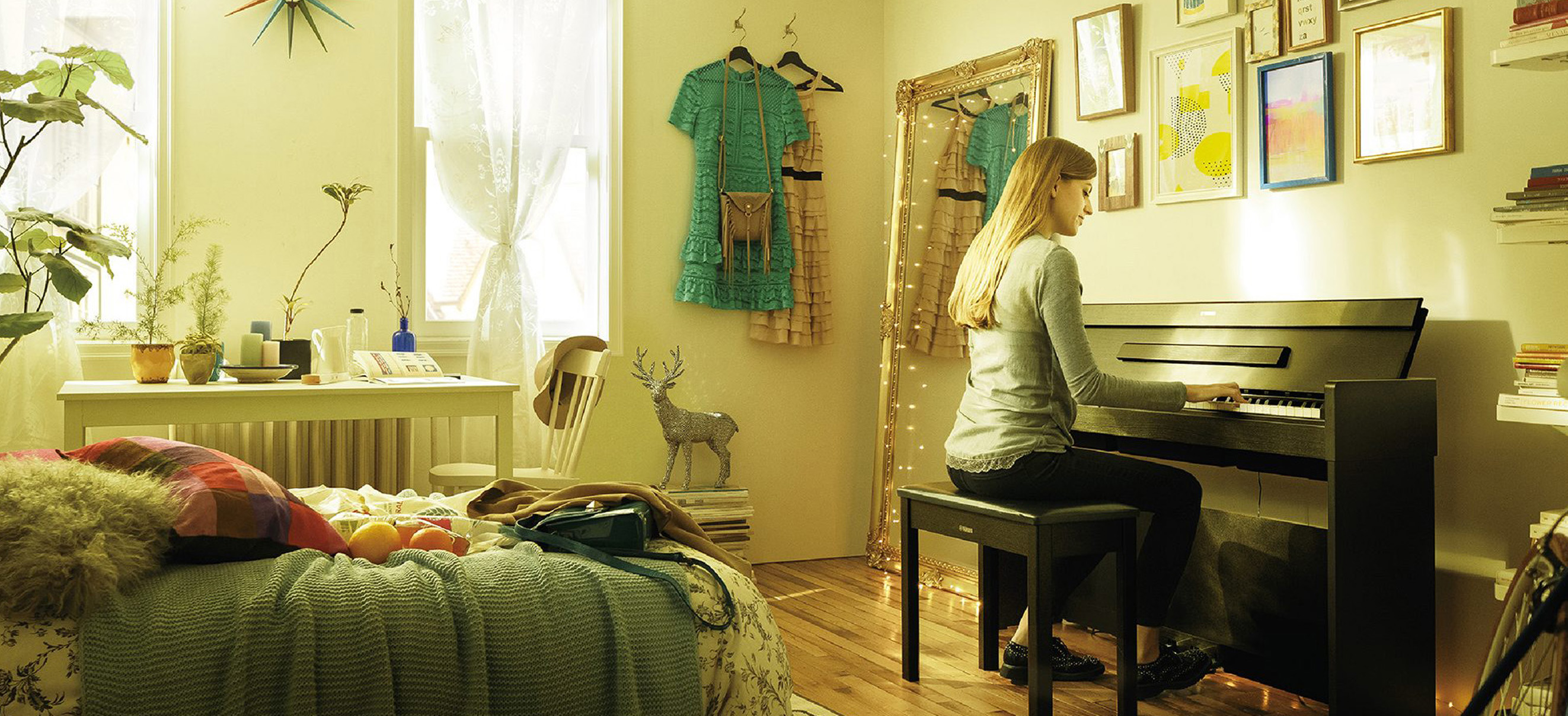 Photo of a young woman playing the YDP-S34 in their studio bedroom